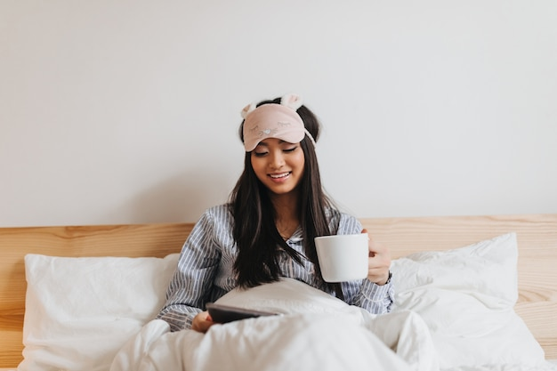 Lady in pajamas and sleeping mask holds cup of tea and reads while lying in bed