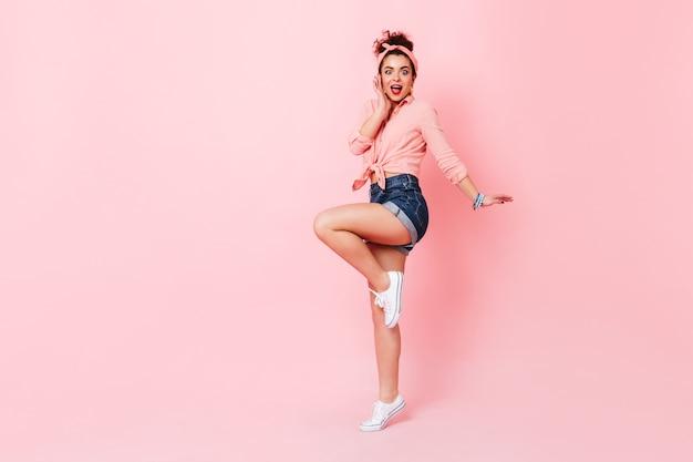 Signora in camicia rosa, pantaloncini di jeans e scarpe da ginnastica salta e guarda la telecamera con sorpresa.