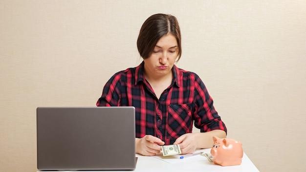 Lady plans budget inserting dollar bill into piggy bank