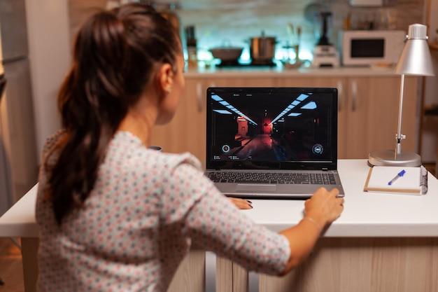 家庭の台所で夜間の夜間にラップトップでゲームをしている女性