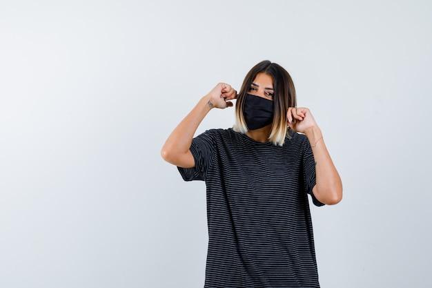 레이디 검은 드레스, 의료 마스크에 손가락으로 귀를 막고 긍정적, 전면보기를 찾고 있습니다.