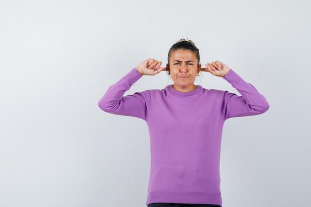 ウールのブラウスに指で耳をふさいでイライラしている女性