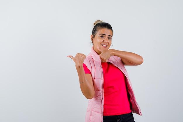 Signora che indica da parte con i pollici in maglietta, gilet e sembra sicura