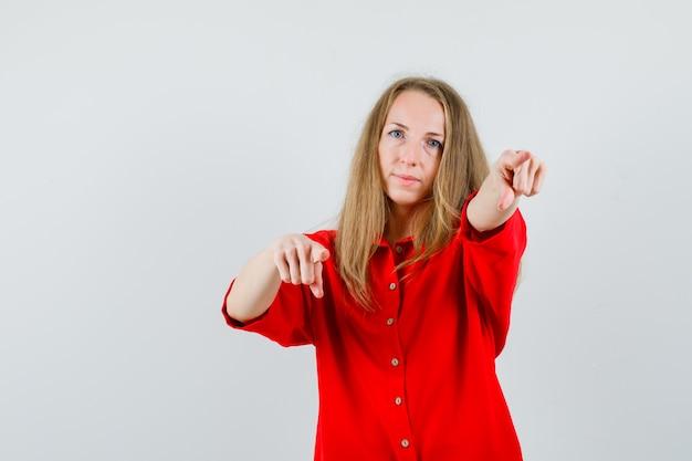赤いシャツを着てカメラを指差して自信を持って見える女性、