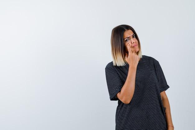 黒のtシャツでまぶたを指差して悲しそうな女性。正面図。