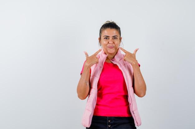 Tシャツ、ベストで彼女の顔を指して自信を持って見える女性