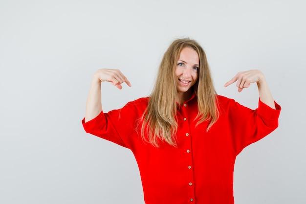 赤いシャツを着て自分を指さし、自信を持って見える女性、