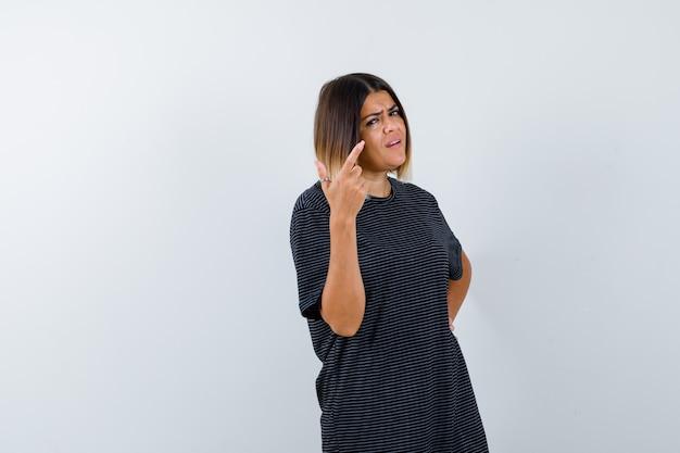 黒のtシャツで右上隅を指して躊躇している女性、正面図。