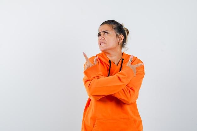 Леди в оранжевой толстовке с капюшоном показывает пальцами в сторону и нерешительно смотрит