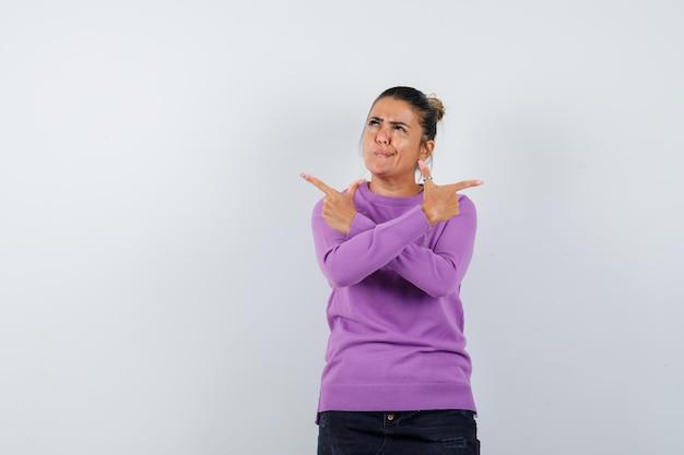 Signora che punta le dita in camicetta di lana e sembra esitante