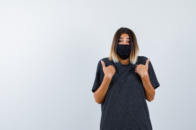 Signora che indica a se stessa in abito nero, mascherina medica e guardando sconcertato, vista frontale.