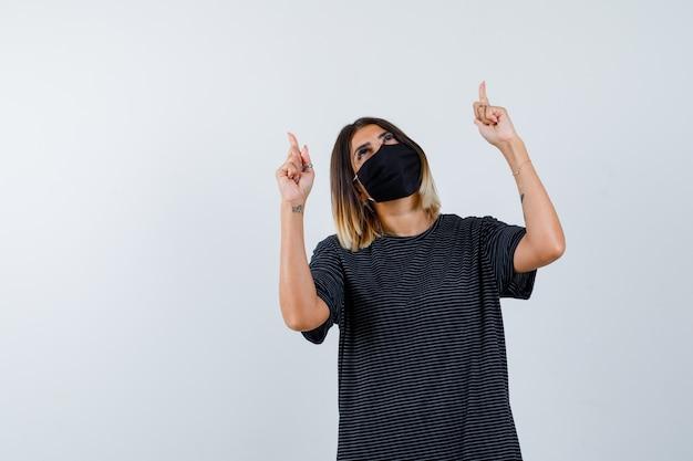 Signora che indica in su in vestito nero, mascherina medica e che sembra speranzosa, vista frontale.