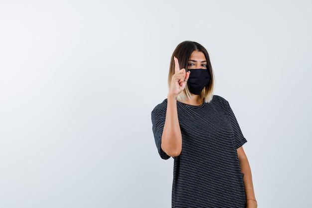 Signora che indica in su in vestito nero, mascherina medica e sembra ragionevole, vista frontale.