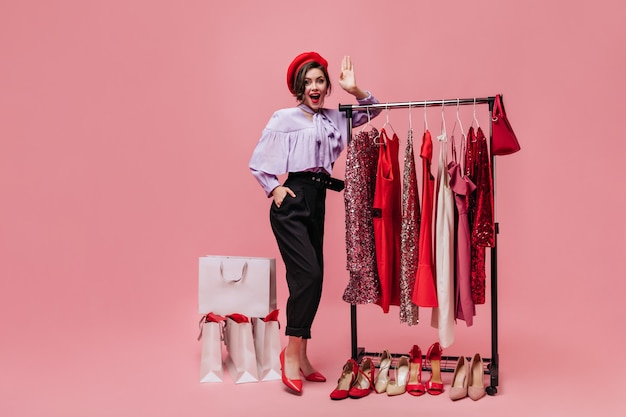 Lady poses in dressing room with bright clothes and shoes. girl in beret and lilac blouse looking at camera on pink background.