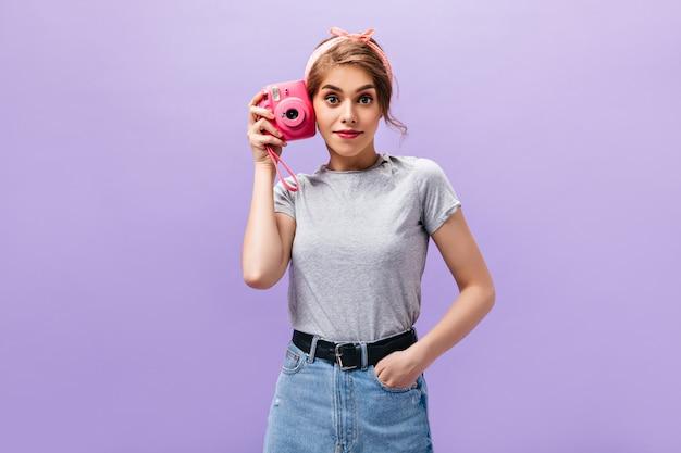 Lady pone con fotocamera rosa su sfondo isolato. bella donna meravigliosa in t-shirt grigia bandana e gonna di jeans con cintura larga fa foto.