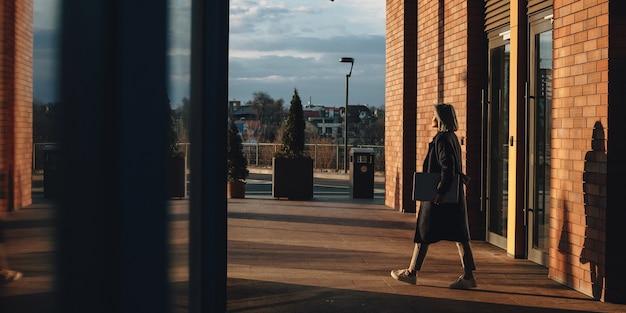 Дама позирует на солнце после окончания рабочего дня и идет домой с компьютером