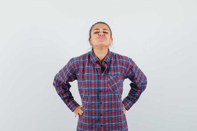カジュアルなシャツを着て唇をふくれっ面にして、かわいく見える女性。正面図。