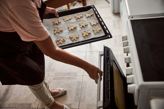 Lady preparing to insert shaped cookie dough into hot oven