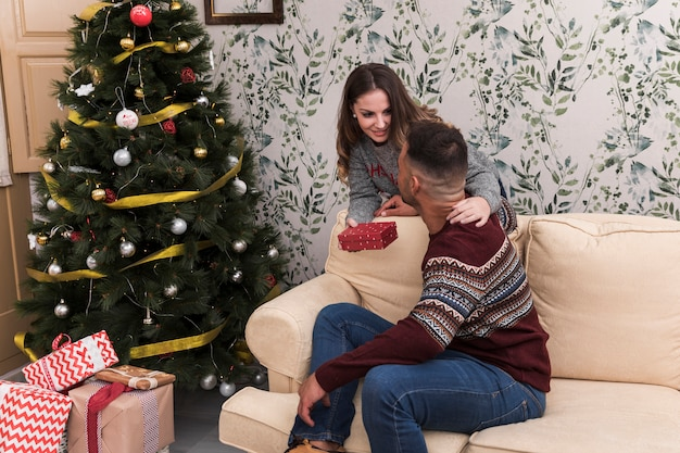 Lady presenting gift box to guy on settee near christmas tree in room