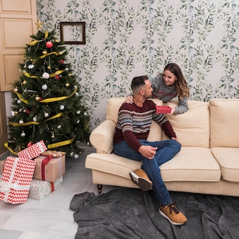 Lady presenting gift to guy on settee near christmas tree