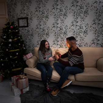 Lady presenting gift packet to guy on settee near christmas tree