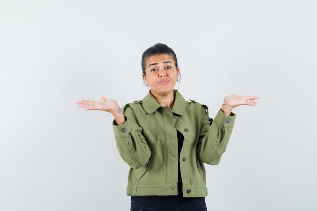 ジャケットで何かを提示または比較する女性