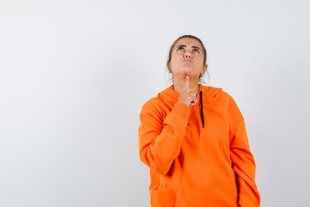Signora che appoggia il mento sul dito in felpa con cappuccio arancione e sembra pensierosa