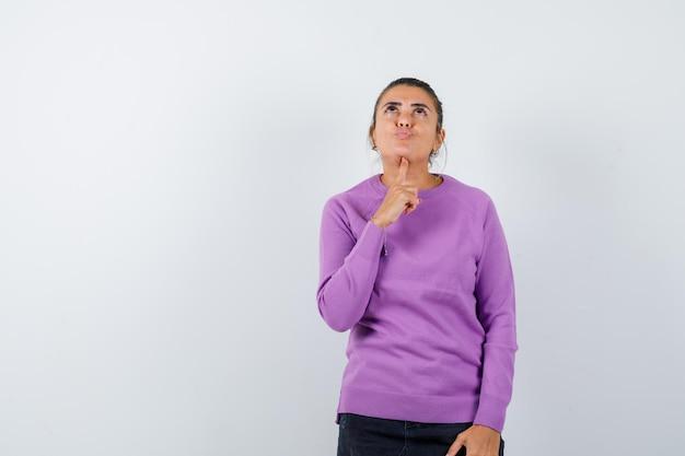 Signora che appoggia il mento sul dito in camicetta di lana e sembra sognante
