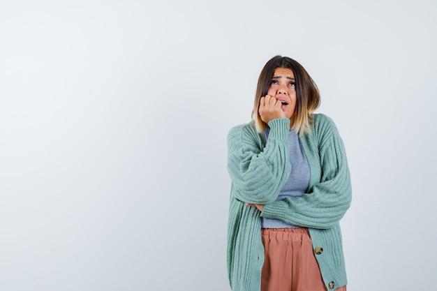 Signora che appoggia il mento a portata di mano in abiti casual e sembra ansiosa. vista frontale.