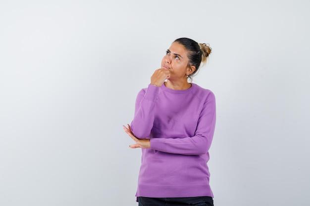 Signora che appoggia il mento sulla mano in una camicetta di lana e sembra pensierosa