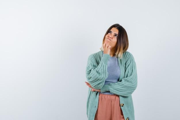 Леди подпирает подбородок рукой в повседневной одежде и смотрит задумчиво, вид спереди.