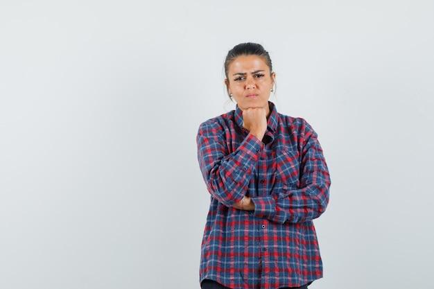 カジュアルなシャツを着て手にあごを支え、悲しそうな正面図の女性。