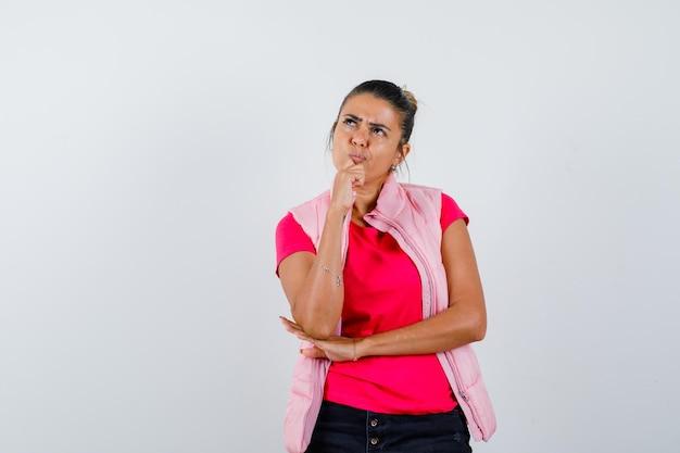Tシャツ、ベスト、物思いにふけるように手に顎を支える女性