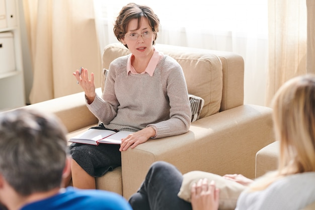 Lady psychologist giving advice to couple in quarrel