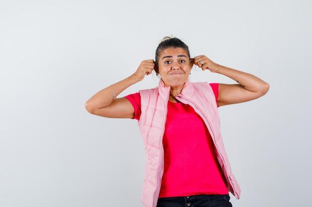 Леди затягивает уши в футболке, жилете и выглядит смешно