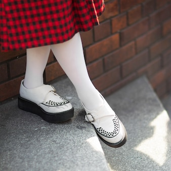 Lady in punk rock style shoes, black and red tartan pattern skirt, white sock with shallow depth of field, focus on shoe