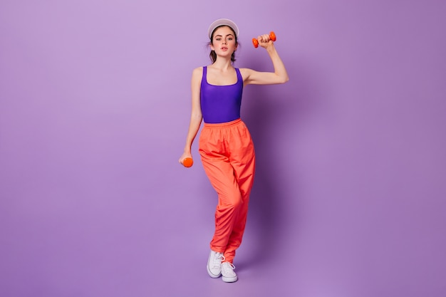 Signora in viola sport top e pantaloni arancioni facendo esercizi per le mani con manubri rossi