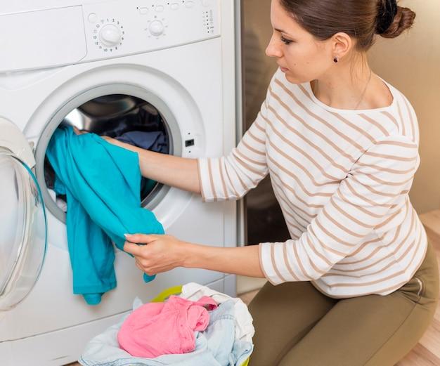 洗濯機に洗濯物を置く女性