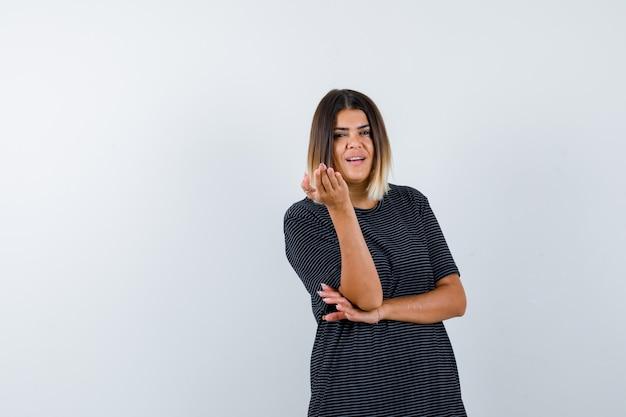 Signora alzando la mano nel gesto interrogativo in maglietta nera e guardando perplesso. vista frontale.
