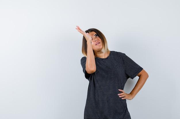 Signora che alza la mano mentre cerca in maglietta nera e sembra pensierosa. vista frontale.