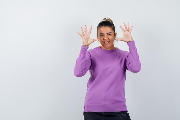 Signora alzando le mani mentre afferra qualcosa in camicetta di lana e sembra allegra