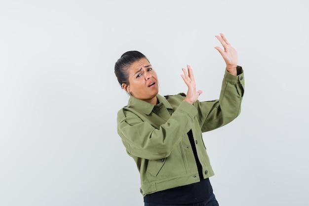 재킷에 예방 방식으로 손을 올리는 레이디