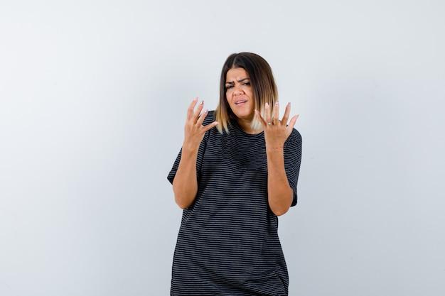 黒のtシャツで困惑したジェスチャーで手を上げて困っている女性。正面図。