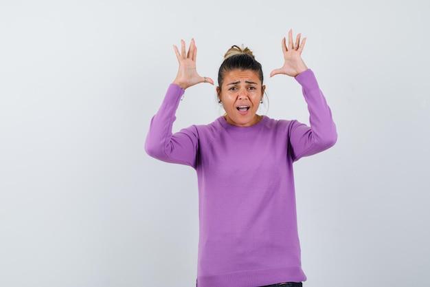 Дама в шерстяной блузке поднимает руки в жесте капитуляции и выглядит встревоженной