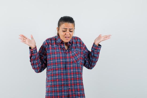 Signora che alza le palme aperte in camicia casual e sembra triste. vista frontale.