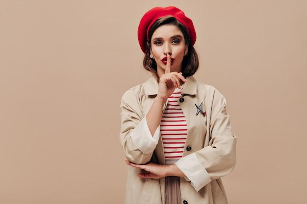 Signora in berretto rosso e trincea beige chiede di mantenere il segreto su sfondo isolato. grave giovane donna con labbra luminose in elegante cappello in posa.