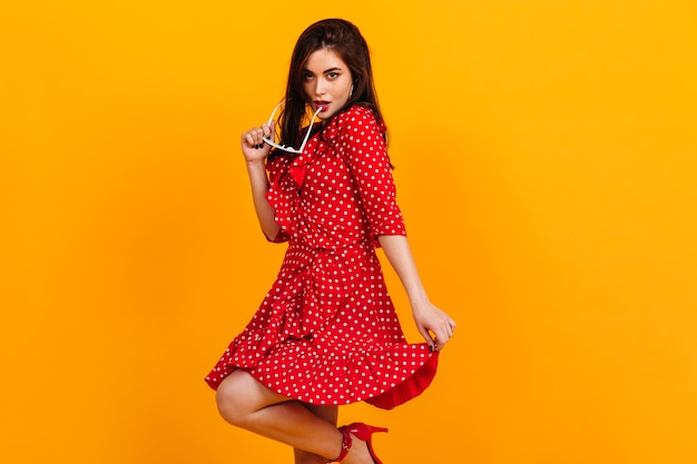 Lady in red polka dot dress flirtatiously posing on yellow wall, taking off her sun glasses.