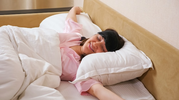 Lady removes sleeping mask stretches arms lying in bed