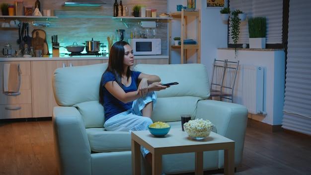 オープンスペースのリビングルームの快適なソファに座って夜に映画を見ながら軽食とジュースで休んでいる女性。リモコンでチャンネルを変更するテレビでリラックスして興奮した面白がって家だけ