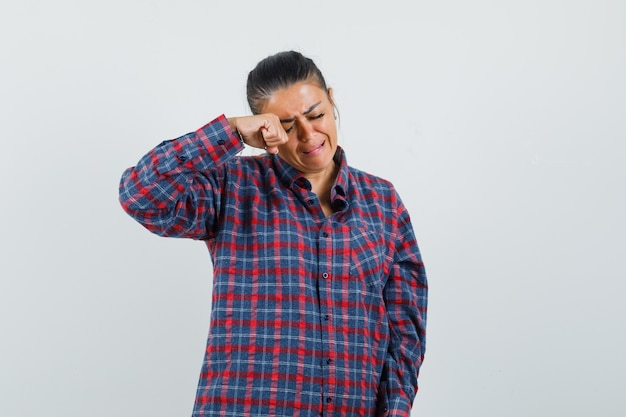 Lady rubbing eye while crying in casual shirt and looking offended , front view.